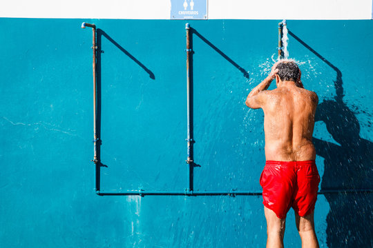 Man using outside showers in the sun, next to beach