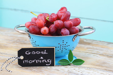 Good morning card with fresh red grapes in blue colander on wooden surface