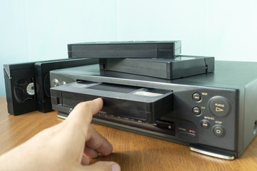 insert a videotape into a tape recorder