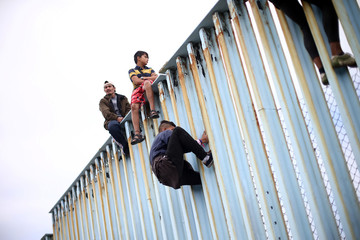 Members of a caravan of migrants from Central America sit on the border fence between Mexico and the U.S. as a part of a demonstration, prior to preparations for an asylum request in the U.S., in Tijuana
