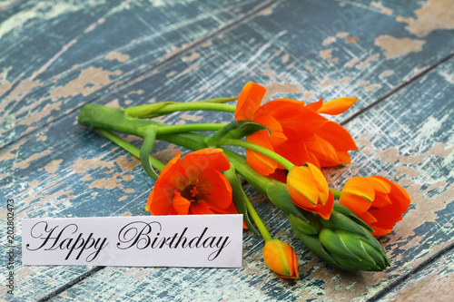 Happy Birthday Card With Orange Flowers On Rustic Wooden Surface