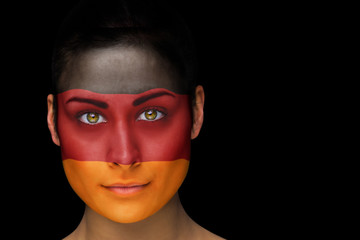 Composite image of german football fan in face paint against black