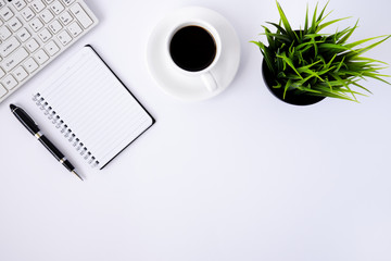 White office desk table with keyboard, notepad, pen, cup of coffee and plant.