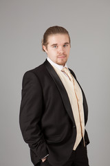 Portrait of handsome smiling young man in a tuxedo. Fashionable clothing for the festive evening