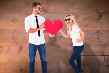 Cool young couple holding red heart against bleached wooden planks background