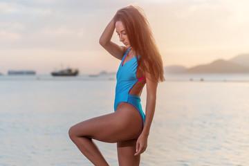 Attractive tanned female tourist in swimwear standing on seashore at seaside resort.