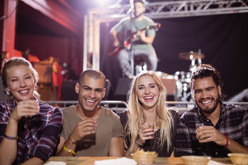 Cheerful friends sitting side by side with musician in background