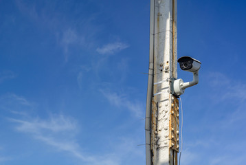 The video camera is watching the post. Blue sky and clouds. Security and control. Copy space.