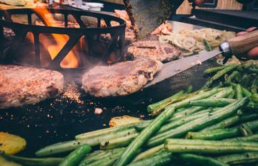Grillgemüse und Burger mit Bacon auf der Feuerplatte grillen
