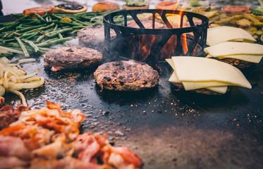 Burger mit Bacon auf der Feuerplatte grillen