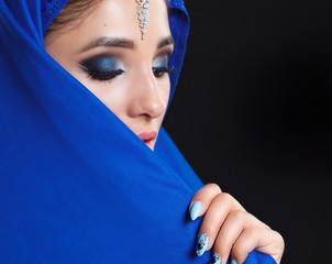 Gorgeous Young East Woman face portrait in hijab. Beauty Model Girl with bright eyebrows, perfect make-up, touching her face. Traditional. Isolated on black background. Smokey.Jewelry on her face