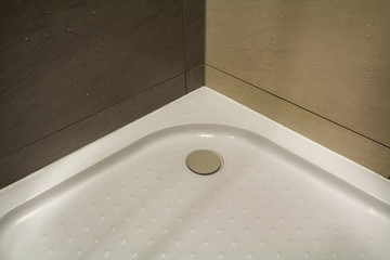 Close-up detail of new modern clean empty white shower cabin with drops of water on nice light beige ceramic tiles on floor and walls. Comfort and hygiene concept.