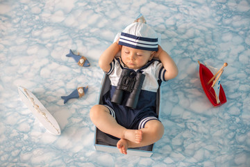 Cute toddler baby boy sleeping in wooden boat with fishes, starfish and binoculars, dressed as sailman