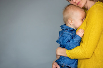 Sad little child, тоддлер boy, hugging his mother at home, isolated image, copy space.