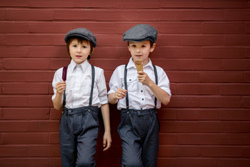 Little preschool boys, cute children, dressed in vintage style clothes, eating ice cream