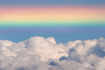 Bright rainbow close-up. Seven-color full spectrum. Photo superimposed cumulus fluffy cloudy on a sky background