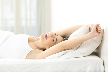 Happy woman waking up stretching arms on a bed