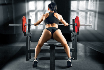 Charming sportswoman sits on a bench in front of a barbell and is preparing to perform an exercise called an army bench press.