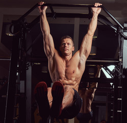 Muscular shirtless man doing push-ups on the horizontal bar in the gym.