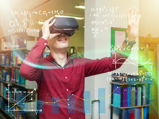 Smart young man in a library travels in a virtual futuristic world with augmented reality. Concept:...