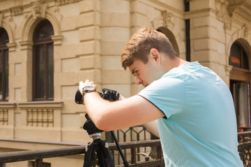 Young photographer with a tripod making photos in city