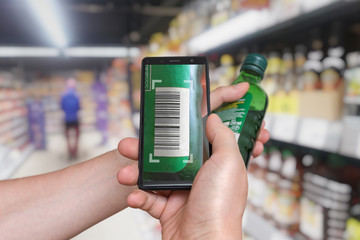Man is shopping in supermarket and scanning barcode with smartphone.