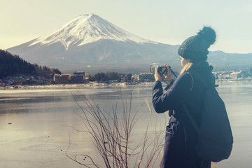 Asian young woman tourist backpacker take landscape photo at fuji mountain and village view in Japan, clear sky with blank copy space