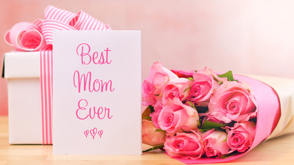 Happy Mother's Day gift, pink roses and Best Mom Ever greeting card on table.