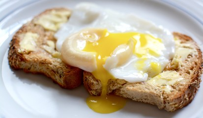 Runny poached egg on brown buttered toast