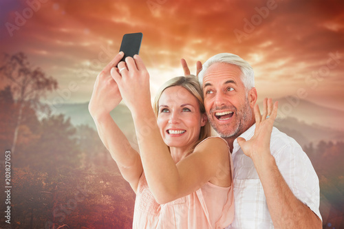 Happy Couple Posing For A Selfie Against Sunrise Over Mountains