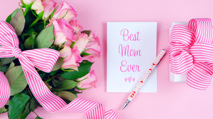 Happy Mother's Day overhead with roses, Best Mom Ever card and gift on pink wood table.