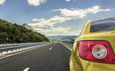 Yellow car rushing along a high-speed highway.