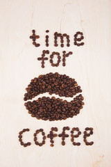 """Inscription """"Time for coffee"""" made from many roasted coffee beans on wooden background"""
