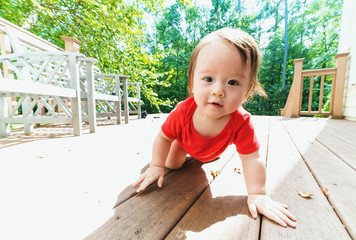 Happy toddler boy crawling and playing outside