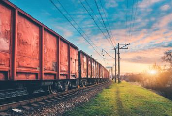Red cargo wagons and train on railway station against blue sky with clouds at sunset. Colorful industrial landscape with railroad. Railway platform. Heavy industry. Cargo shipping. Transportation