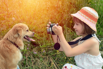 Little girl photographer taking pictures of a dog in nature.
