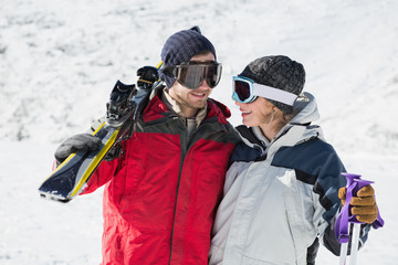 Happy young couple with ski boards on snow