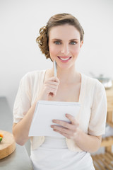 Cheerful woman thinking while writing the shopping list in her kitchen