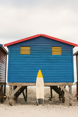 Surfboard by blue wooden hut on sand at beach