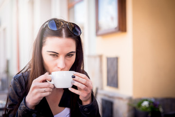 The woman is drinking coffee and tea. The girl puts a cup of coffee into her mouth. Relax in the cafe.