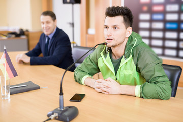 Portrait of young professional sportsman speaking to microphone at press conference
