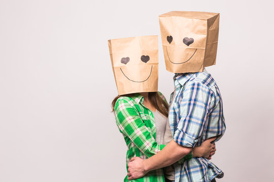 Valentine's day concept - Young love couple with bags over heads on white background with copyspace