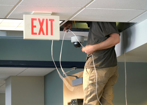 technician installing security camera in the office