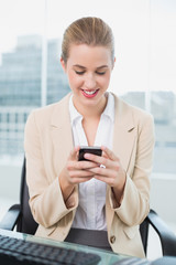 Smiling attractive businesswoman text messaging