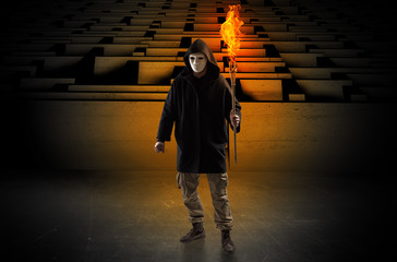 Ugly, aberrant man coming out from the labyrinth with burning flambeau on his hand