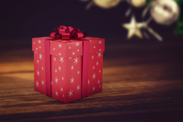 A red Christmas gift with ribbon on wooden background