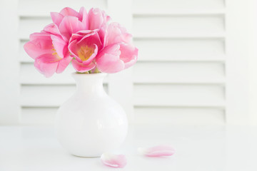 Photograph of a white vase filled with pink tulips on white