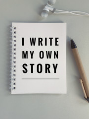 Motivational and inspirational quote - 'I write my own story' on white notebook . With vintage styled background.