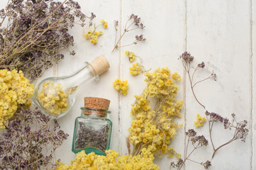 Medicinal herbs in glass jars on light backgrounds