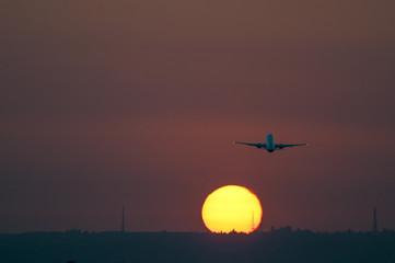 Airplane taking off at Seville airport at sunset